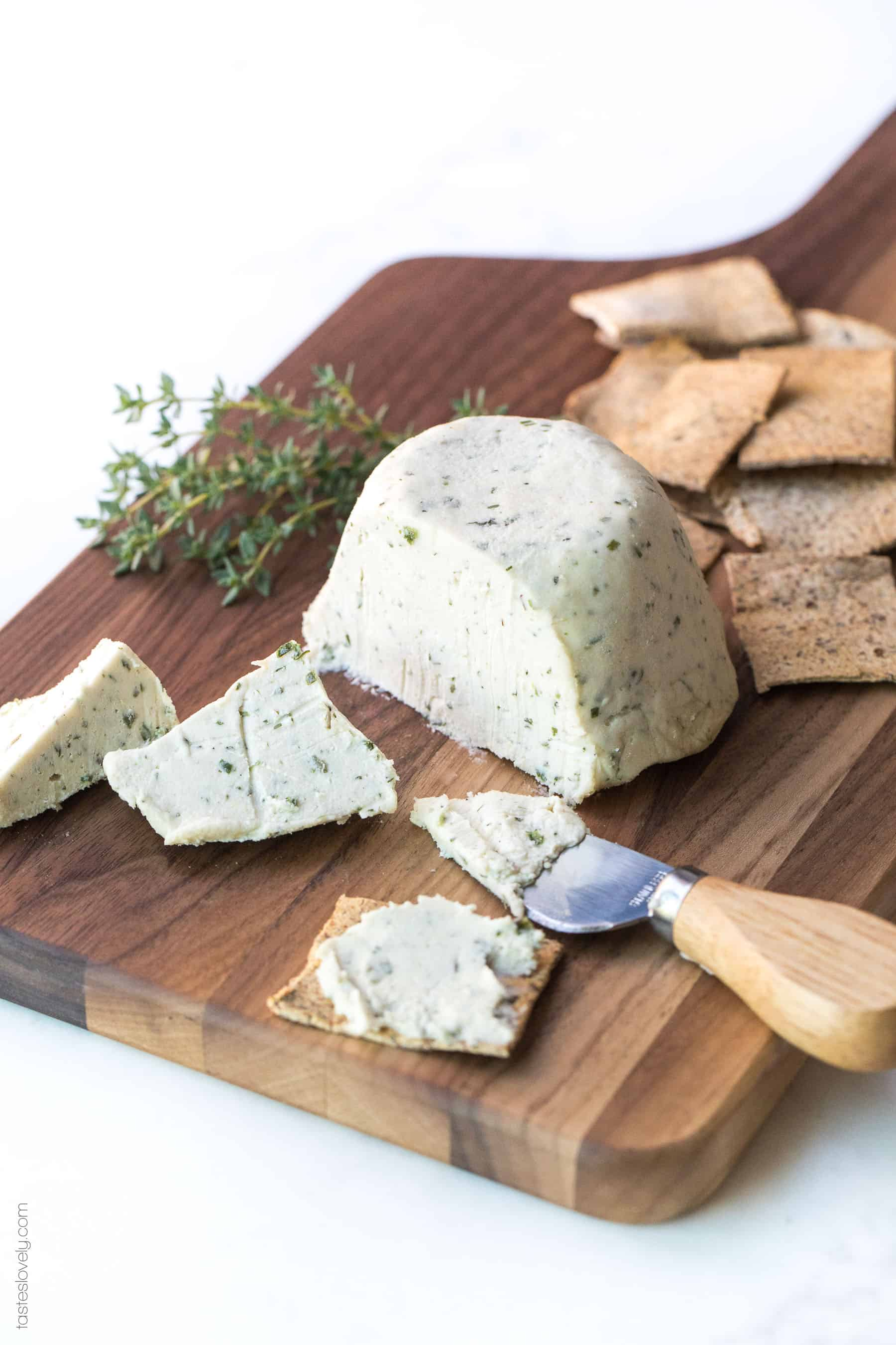 Cheese on a board sliced with crackers and herbs