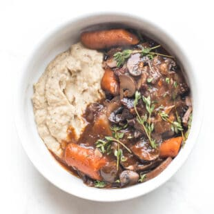 keto instant pot coq au vin with mashed cauliflower in a white bowl on a white background