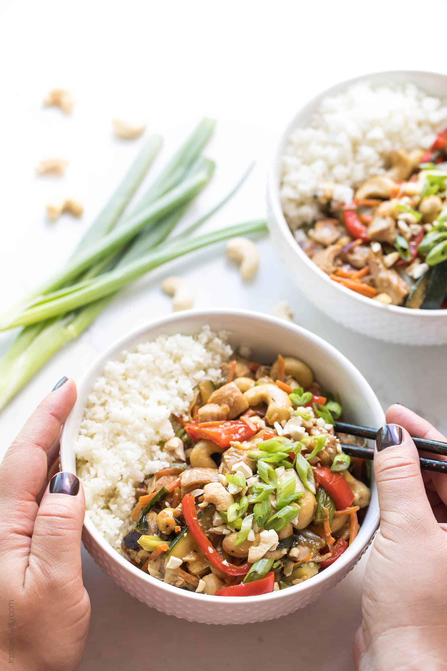 2 hands holding a bowl with chicken stir fry and cauliflower rice and chopsticks