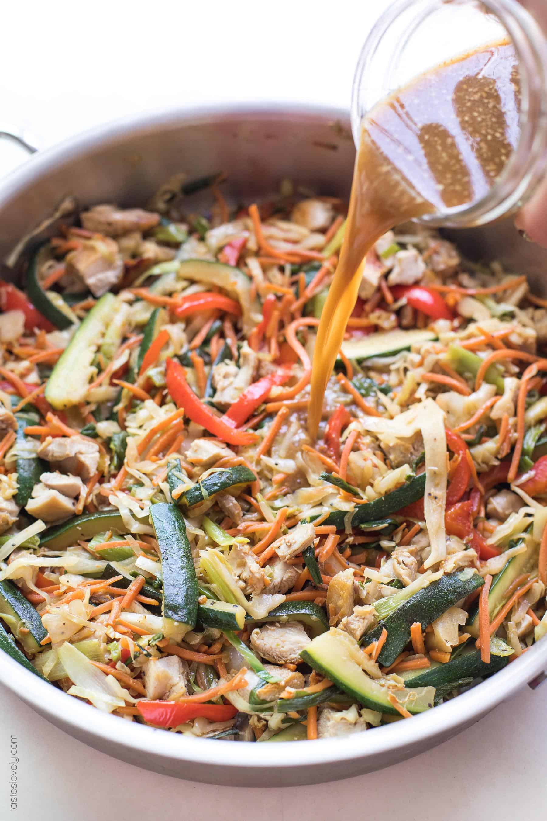 Stir fry sauce poured into a pan of chicken stir fry