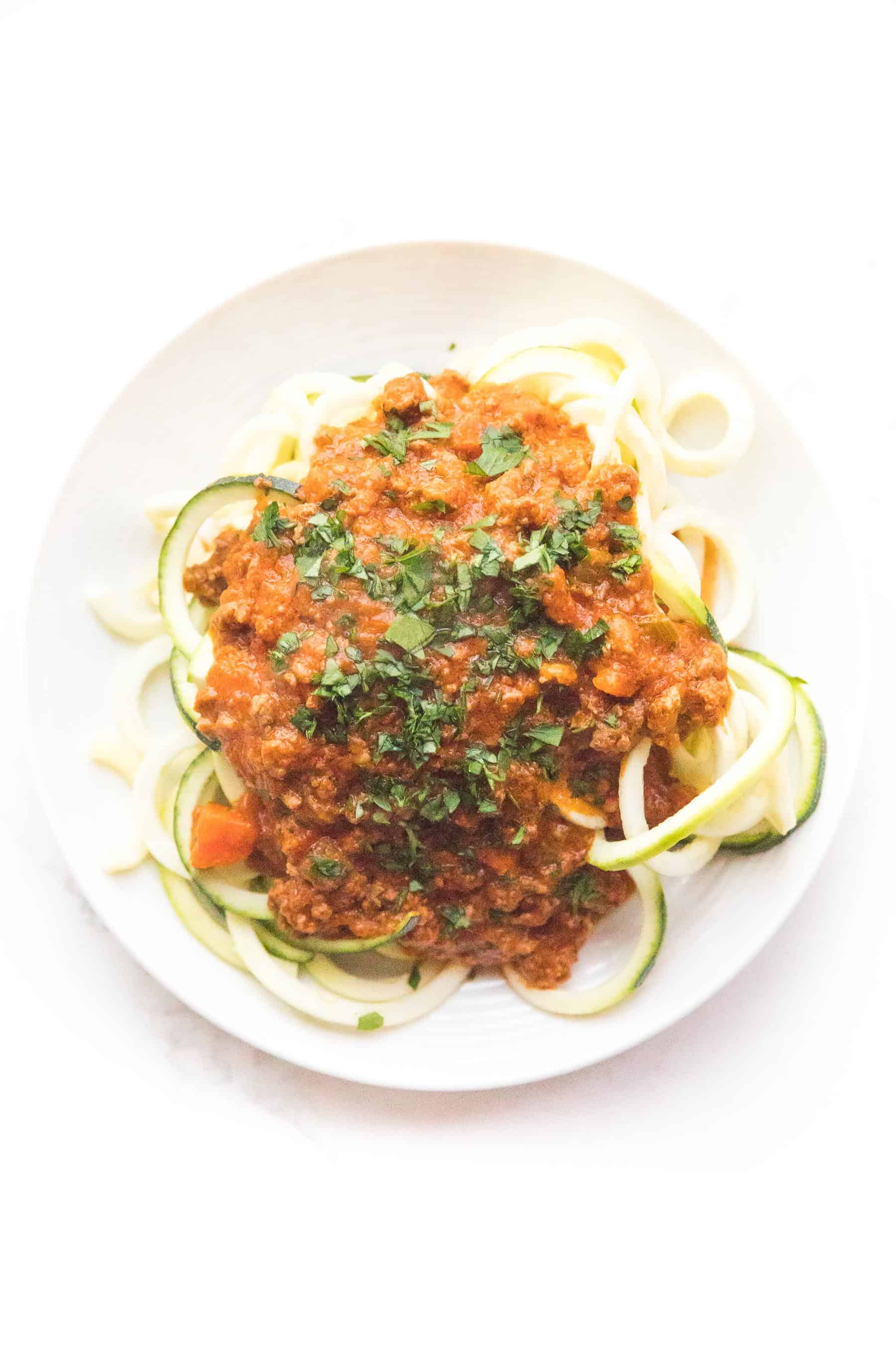 Zucchini noodles with red bolognese sauce on a white plate and background