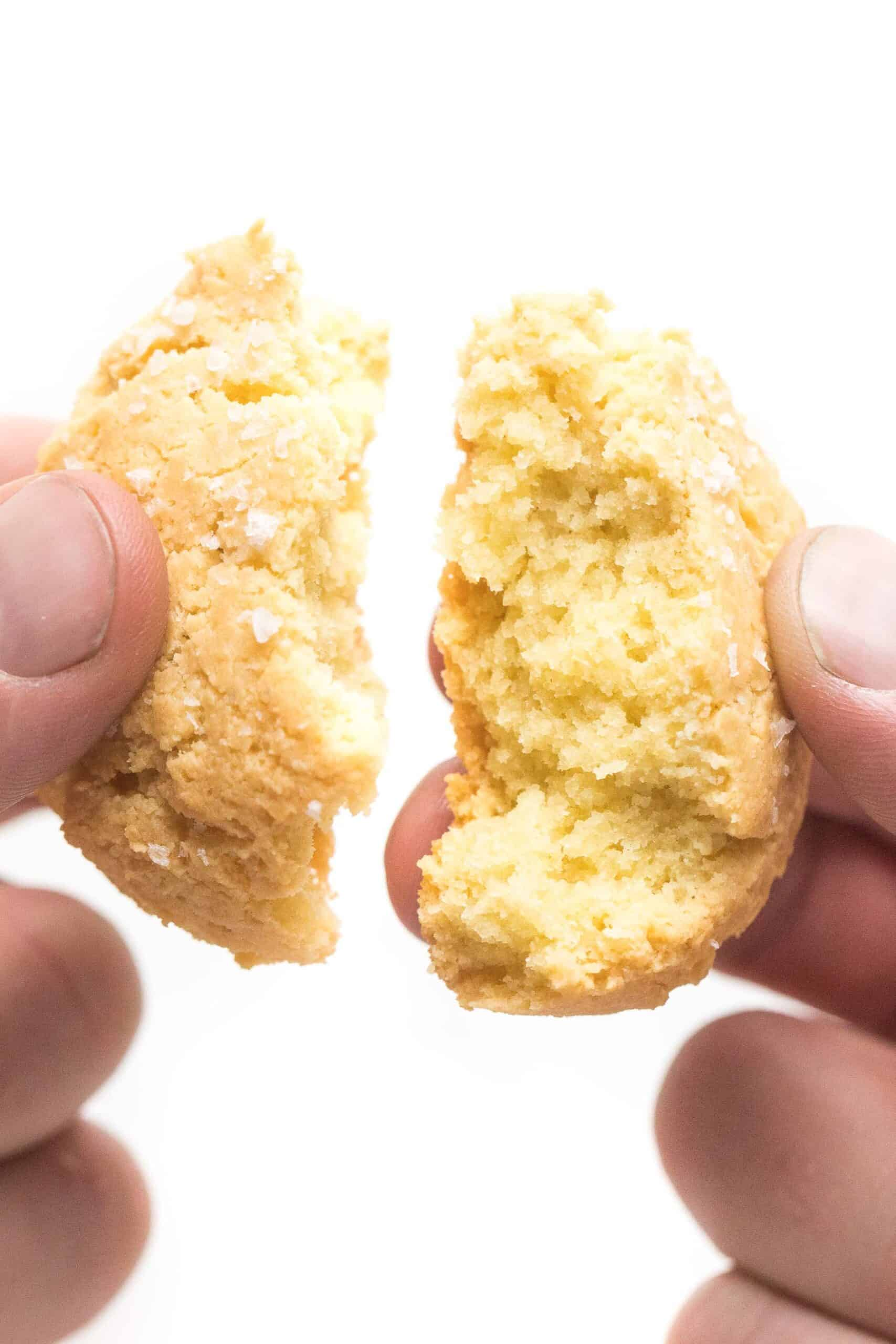 hand breaking apart a keto biscuit on a white background