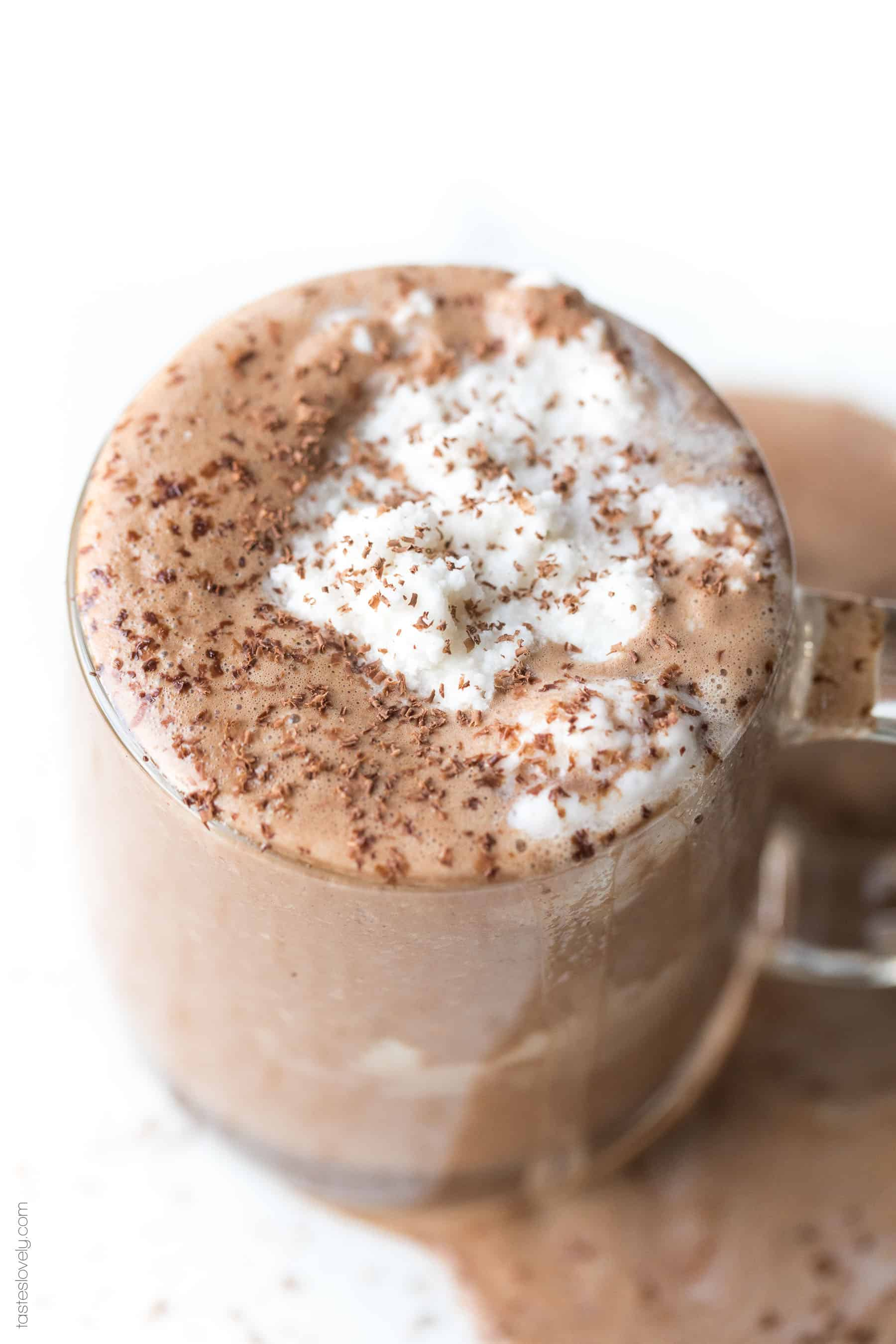 Hot chocolate in a clear mug topped with whipped cream and shaved chocolate