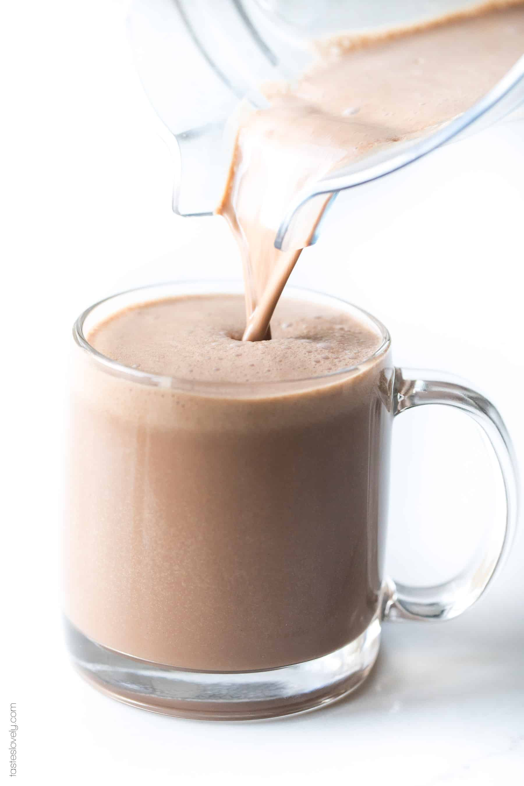 pouring hot chocolate into a clear mug
