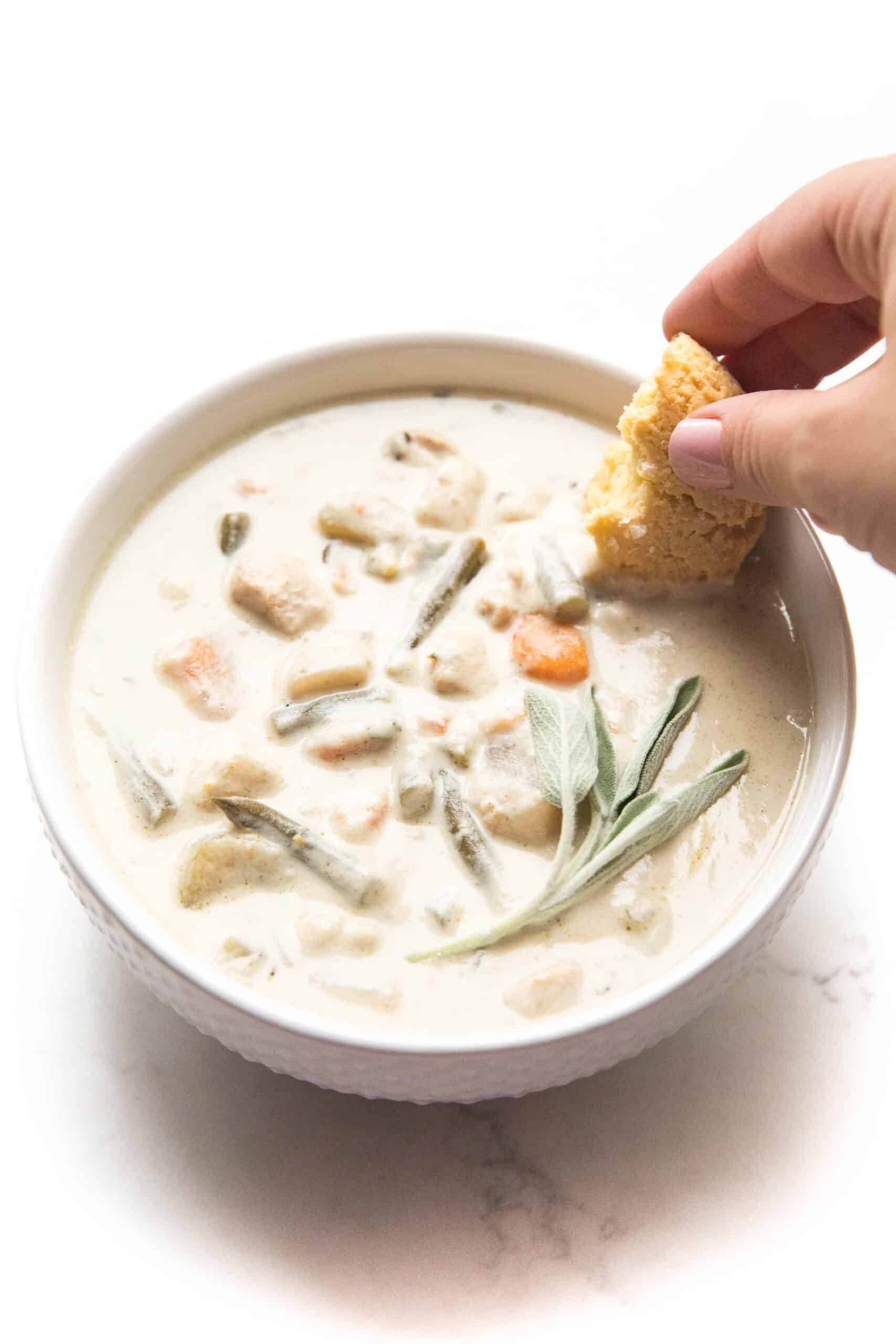 dipping a keto biscuit in creamy chicken chowder in a white bowl + background