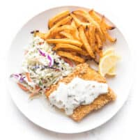fish + chips with coleslaw + tartar sauce on a white plate