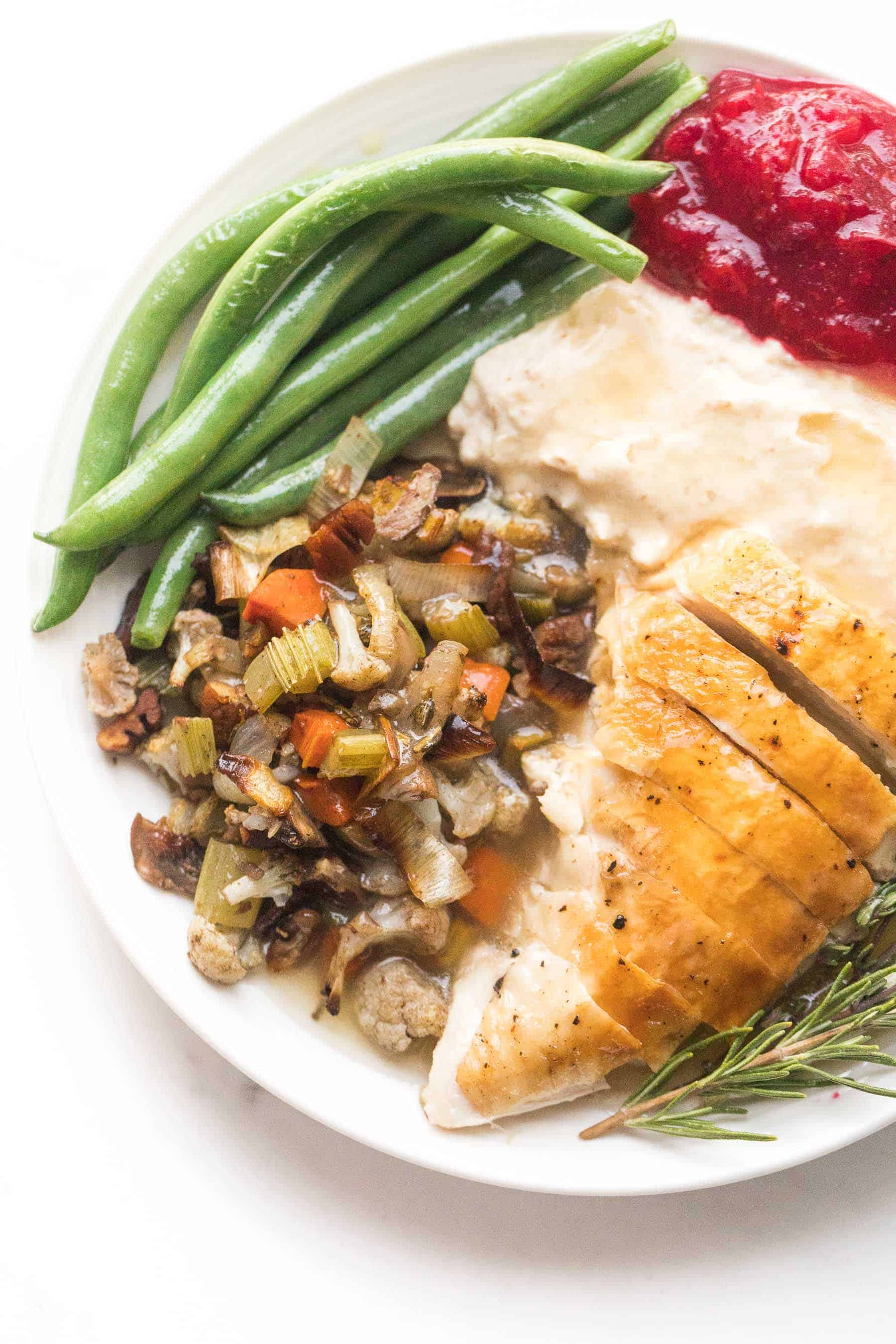 whole30 + keto thanksgiving dinner plate with turkey, cauliflower stuffing, green beans, mashed cauliflower, and keto cranberries