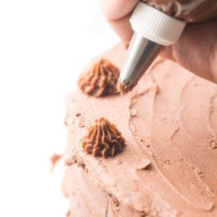 Piping chocolate frosting onto a cake