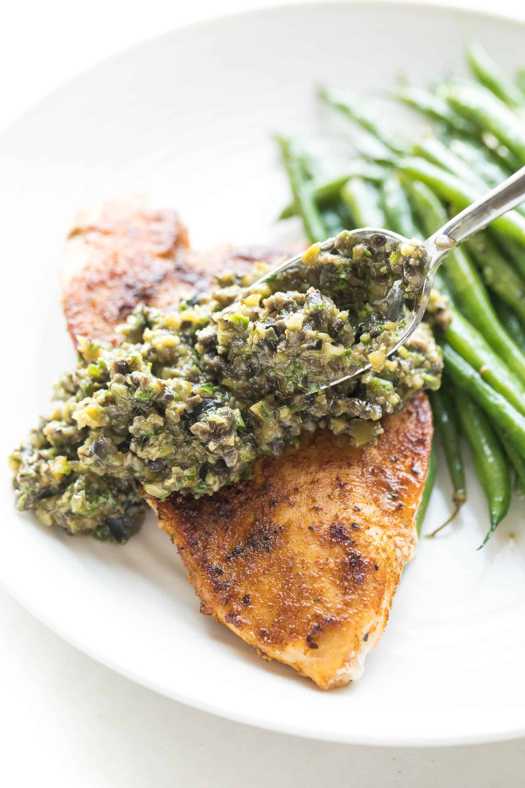 A spoon putting olive tapenade on top of chicken with green beans in the background