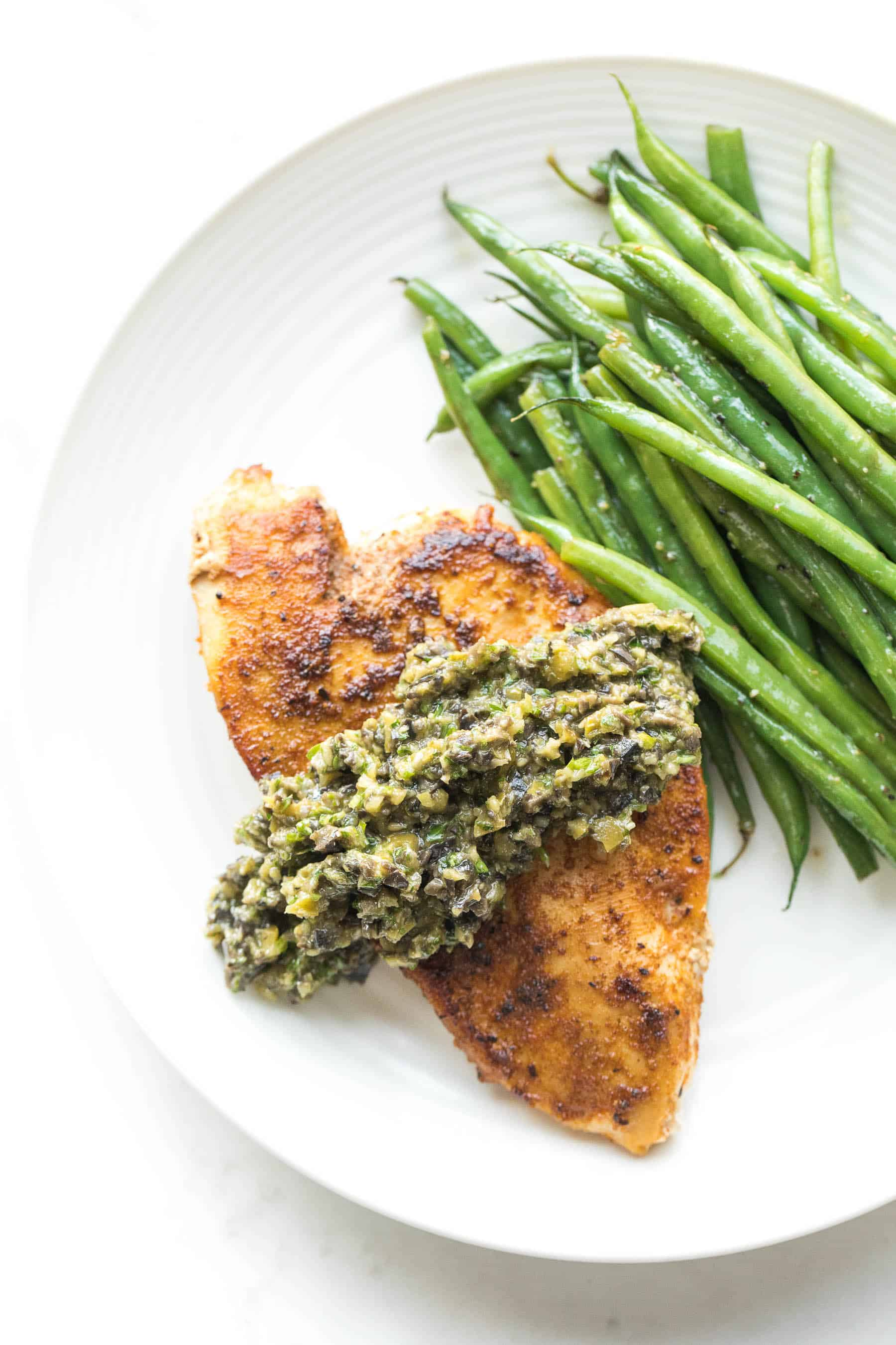 Chicken with olive tapenade and green beans on a white plate
