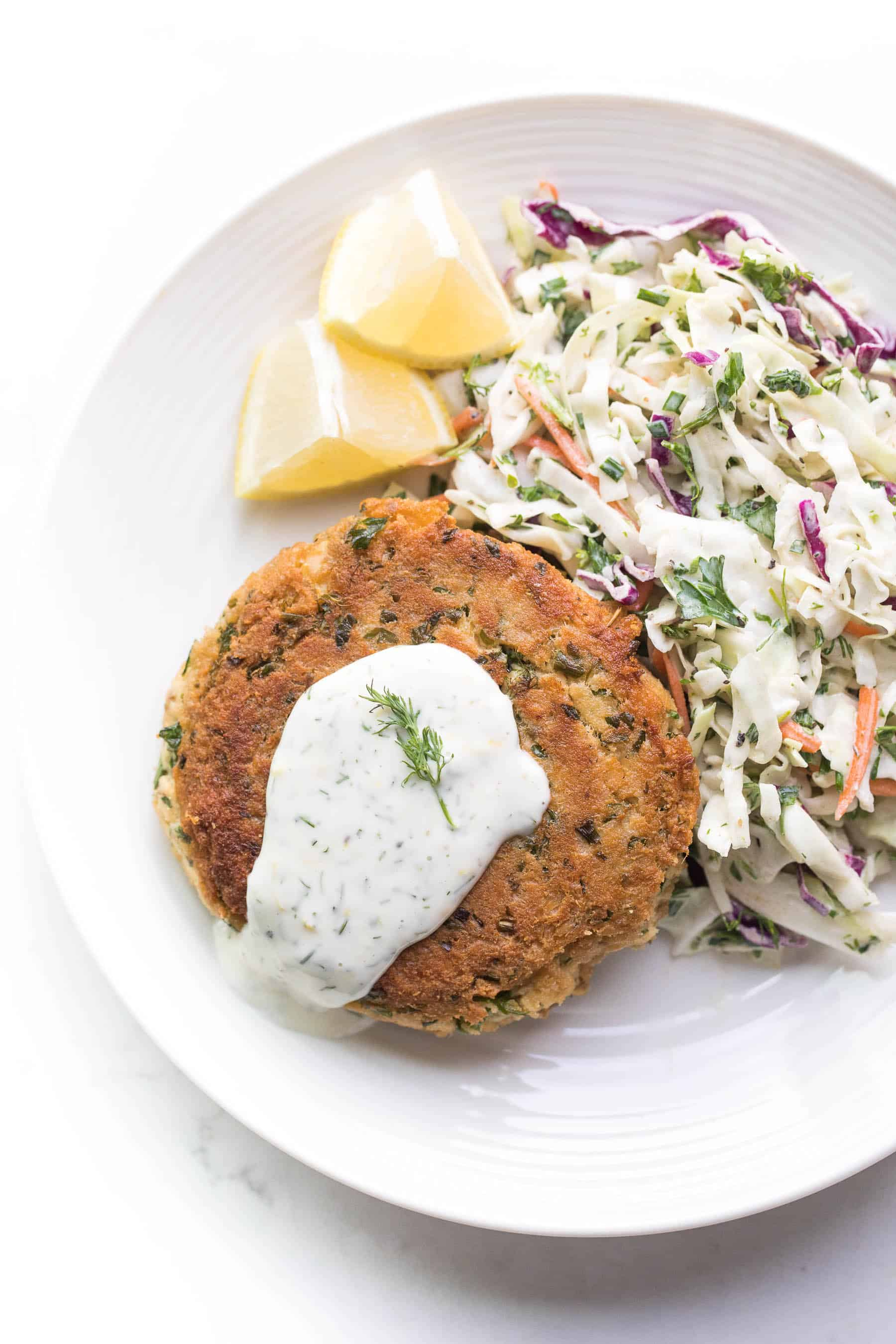 Salmon cake on a white plate with coleslaw and lemon wedges