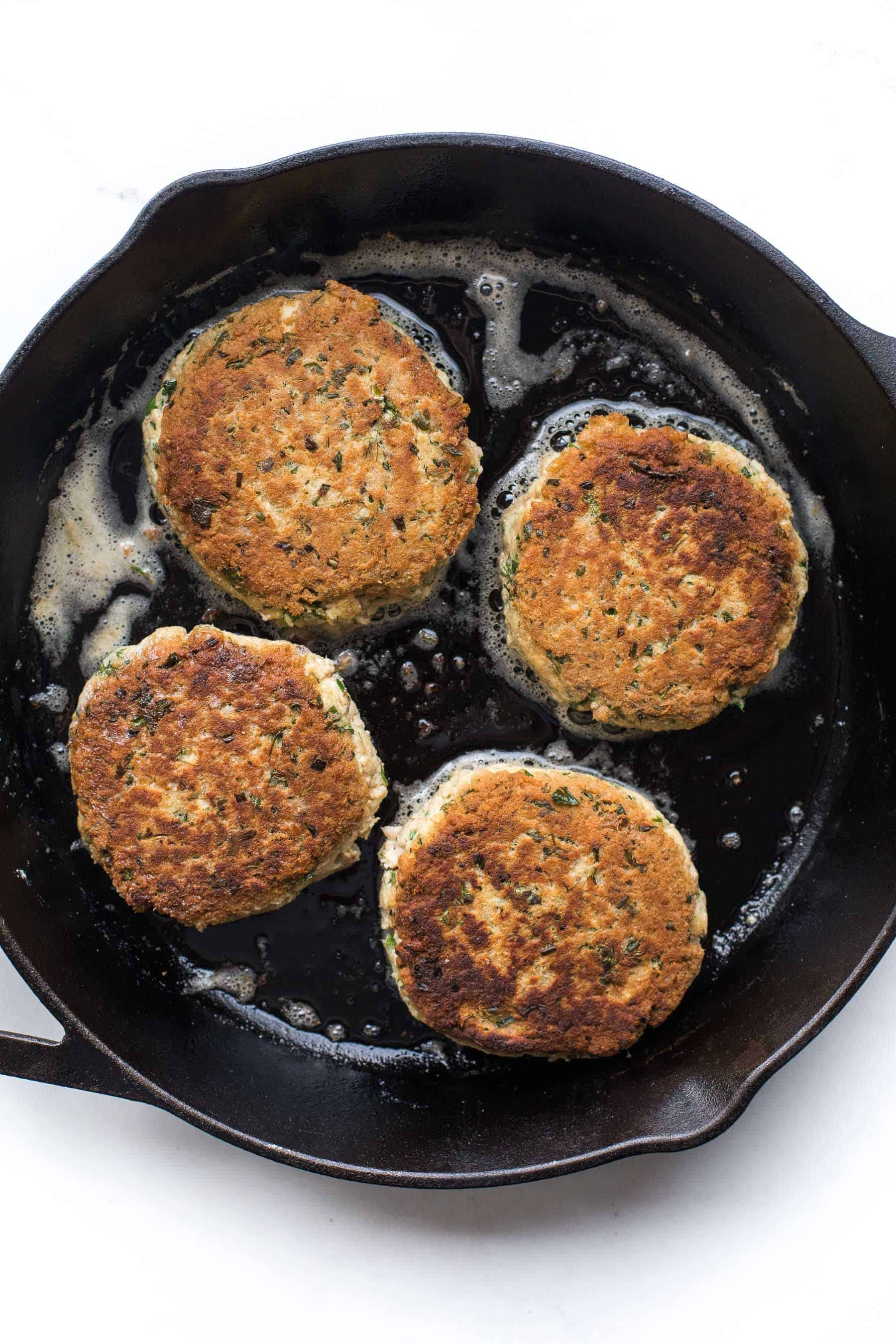 Salmon cakes cooking in a cast iron skillet