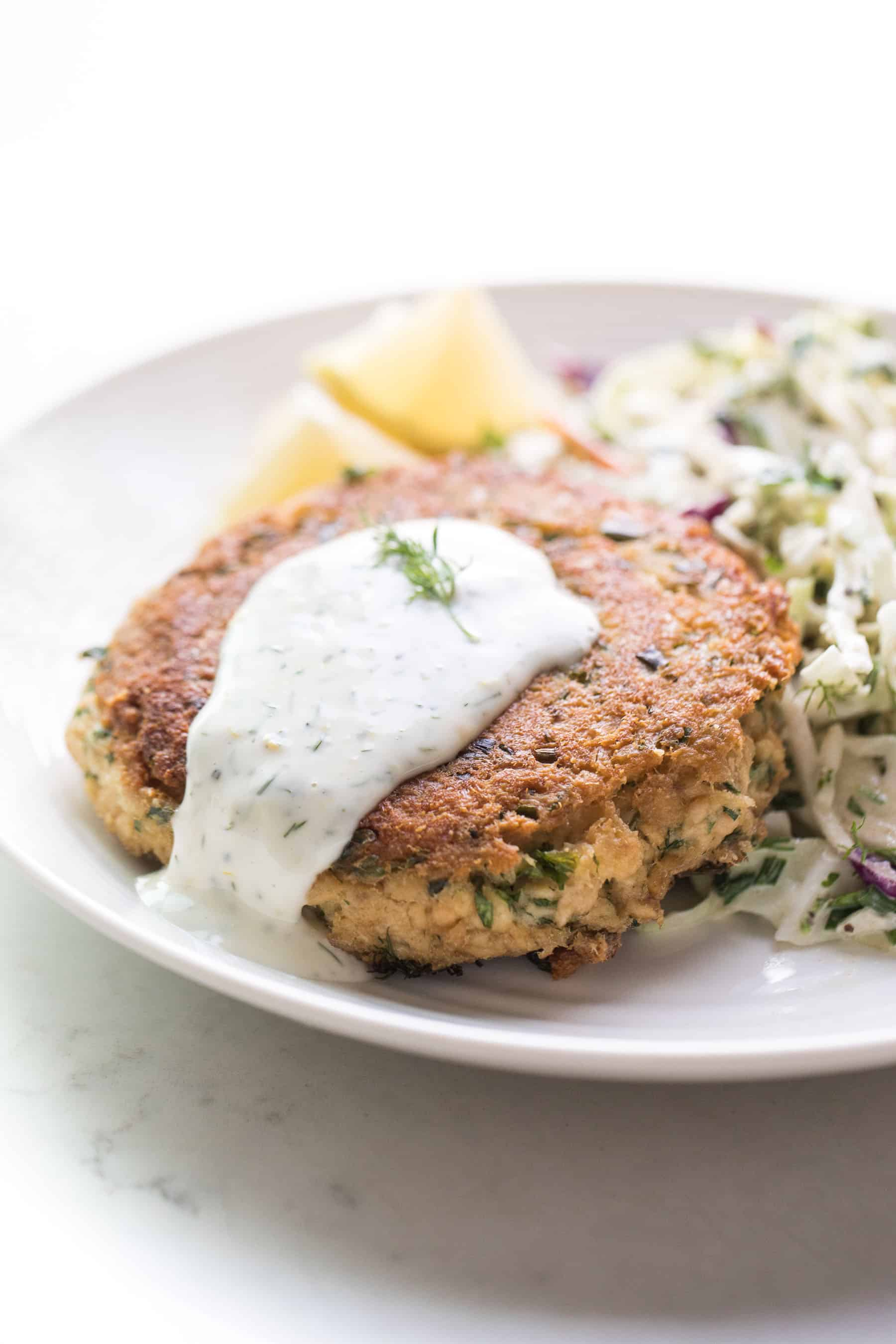 Salmon cake on a white plate with aioli, coleslaw and lemon wedges
