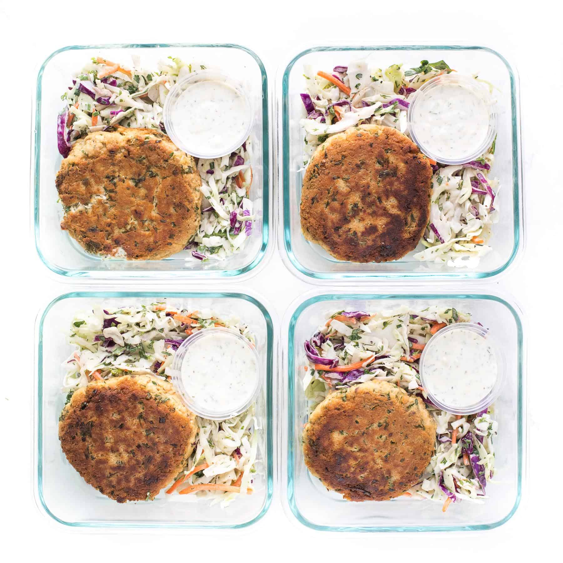 Meal prep of salmon cakes with coleslaw and aioli