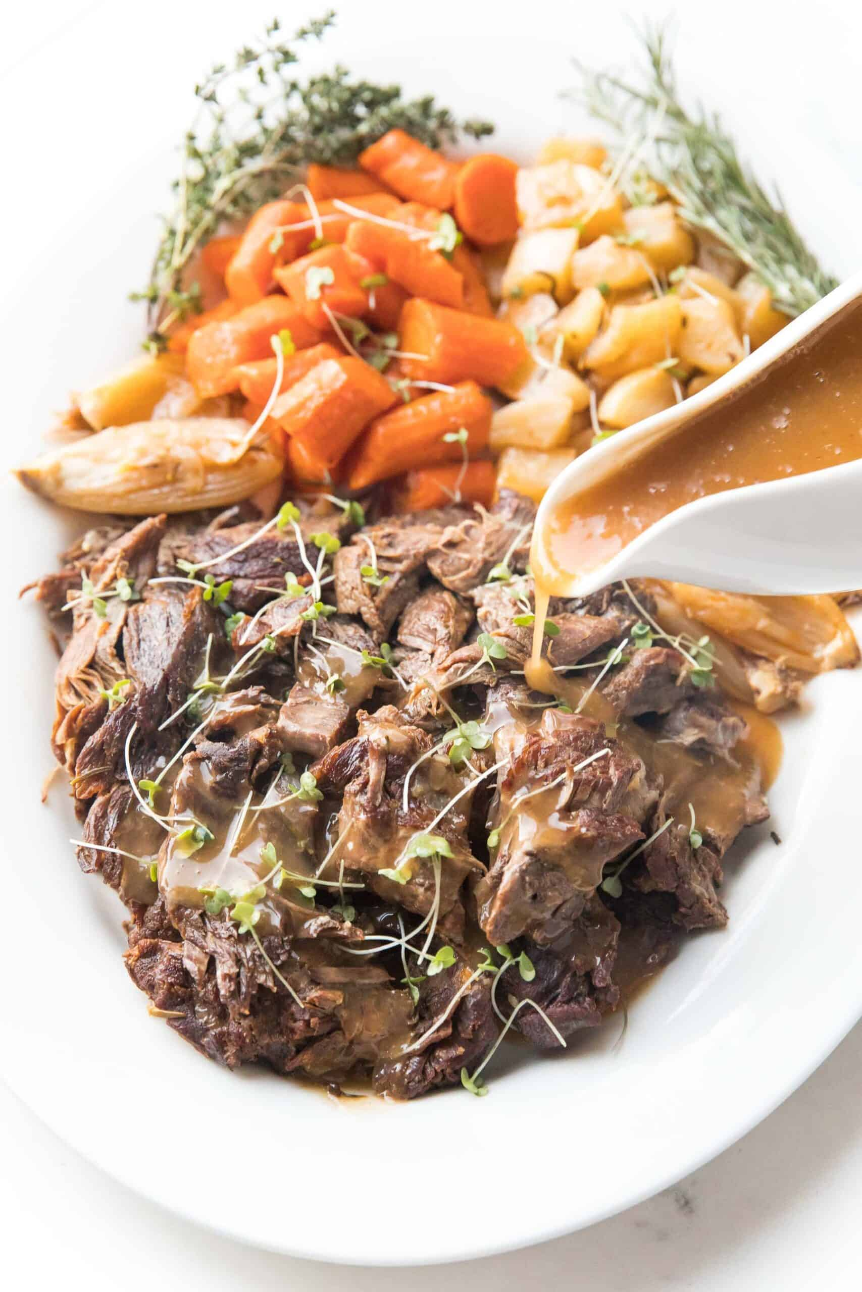 Pot roast + vegetables on a white plate with fresh herbs