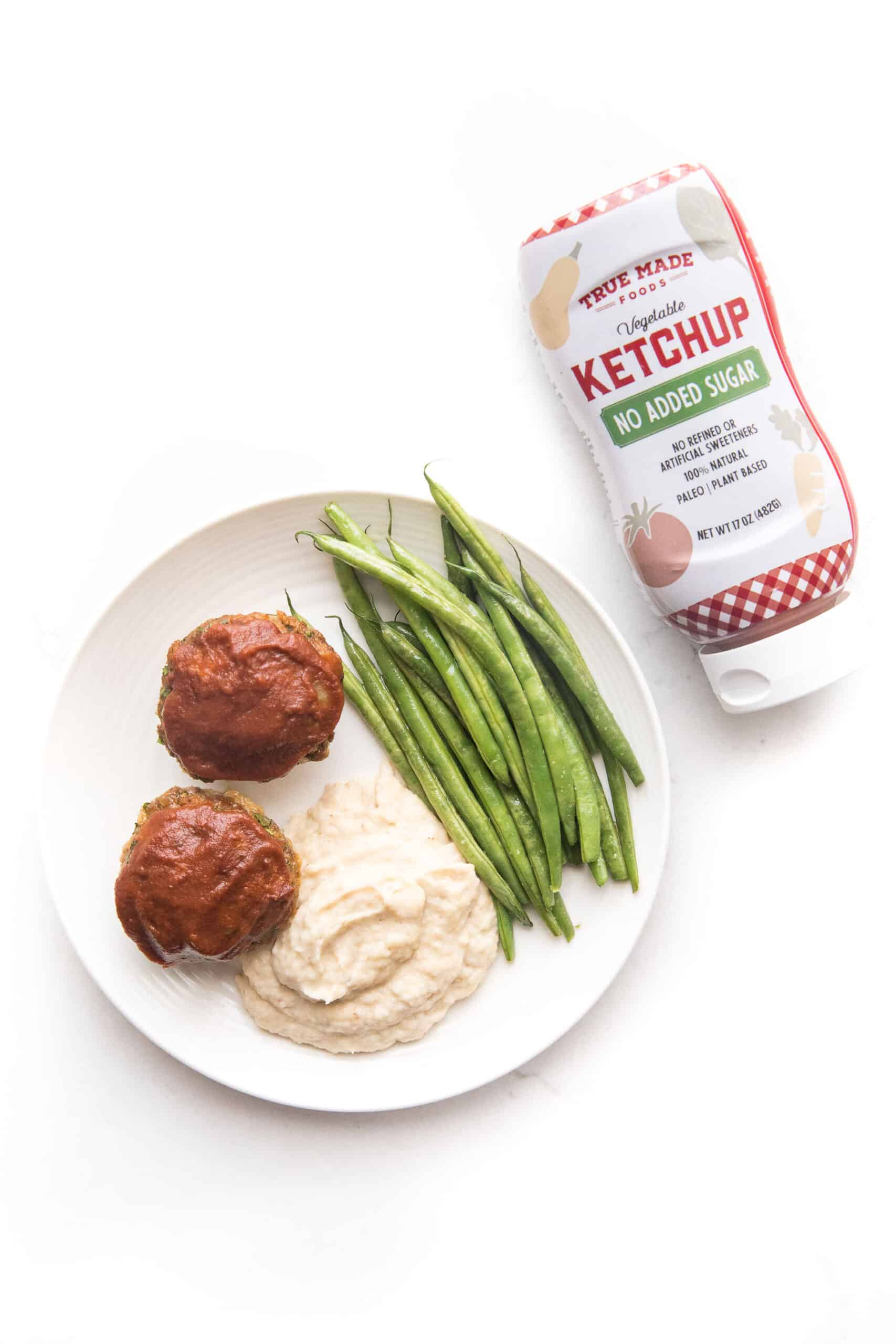 Mini meatloaf muffins topped with ketchup with green beans + mashed cauliflower + green beans on a white plate